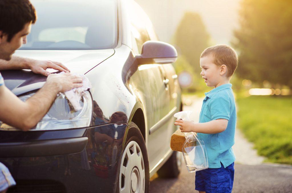 child standing beside vehicle